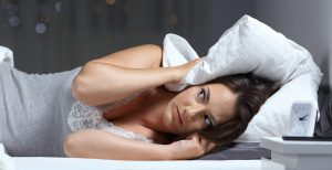 Desperate woman trying to sleep hearing neighbour noises in the night at home